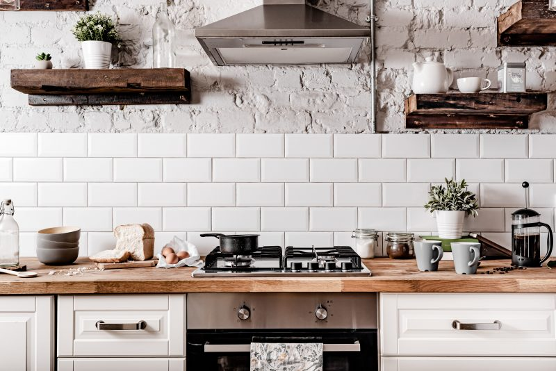 Farmhouse style kitchen in fresh white colors that has a rustic feel