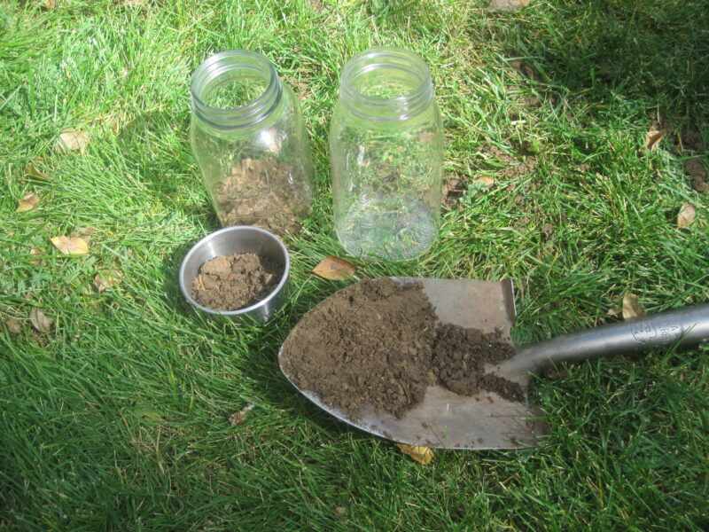samples of soil on a small shovel and glass jar for a simple pH test