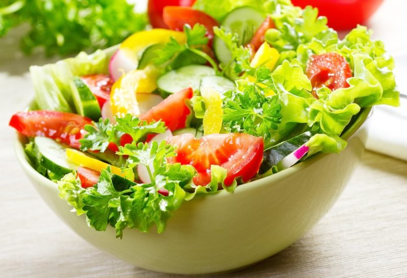fresh lettuce, cucumbers, pepper strips, parsley and tomatoes in a light yellow salad bowl