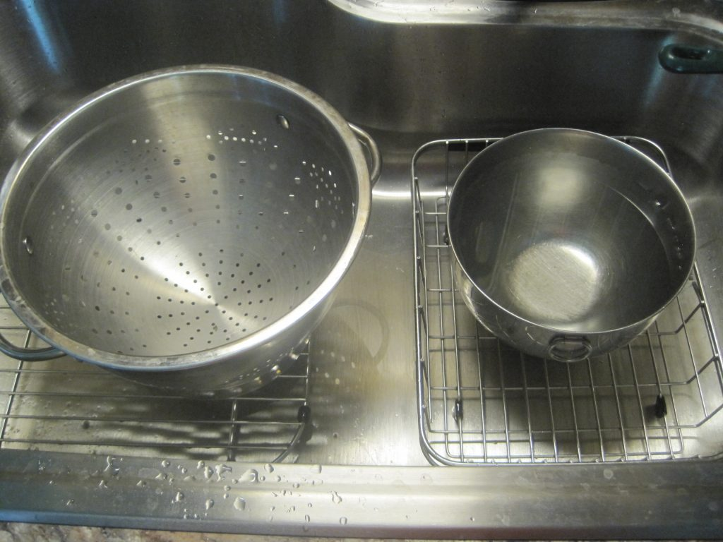 Having a stainless steel strainer and a large bowl of ice water ready to cool down the blanched kale prior to putting in freezer bags or glass jars.