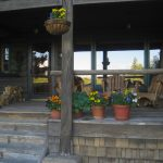 Front Porch with flowers and wooden rocking chairs is welcoming and relaxing looking.