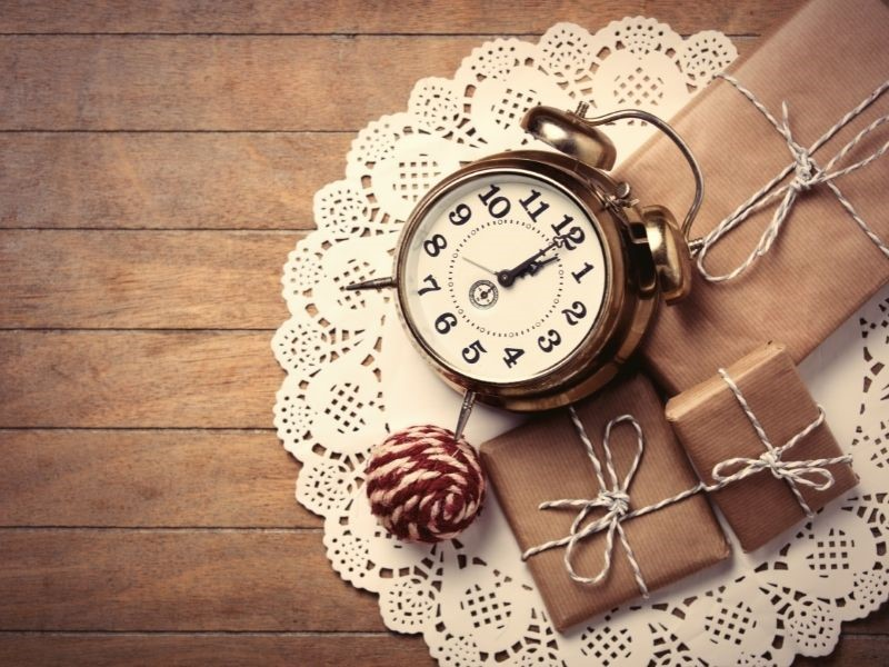 simple clock with gifts wrapped in brown paper for gifts of time