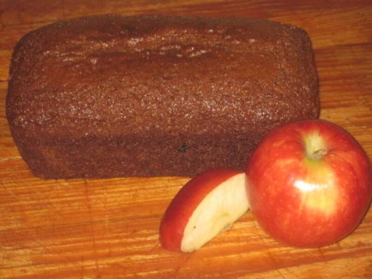 loaf of fresh applesauce bread with apple and apple slices