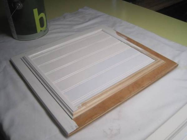 Kitchen cabinet door being painted white as one of the farmhouse kitchen remodel ideas