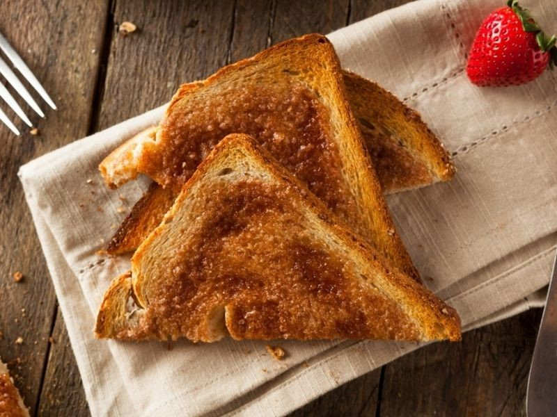 slices of toast on a linen napkin for with a strawberry and a fork