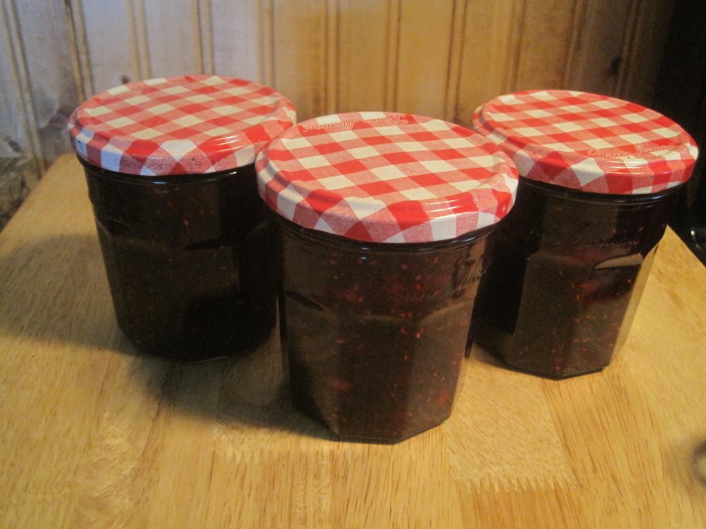 Jars pf Low Sugar Mixed Berry Jam ready to be stored in the refrigerator.
