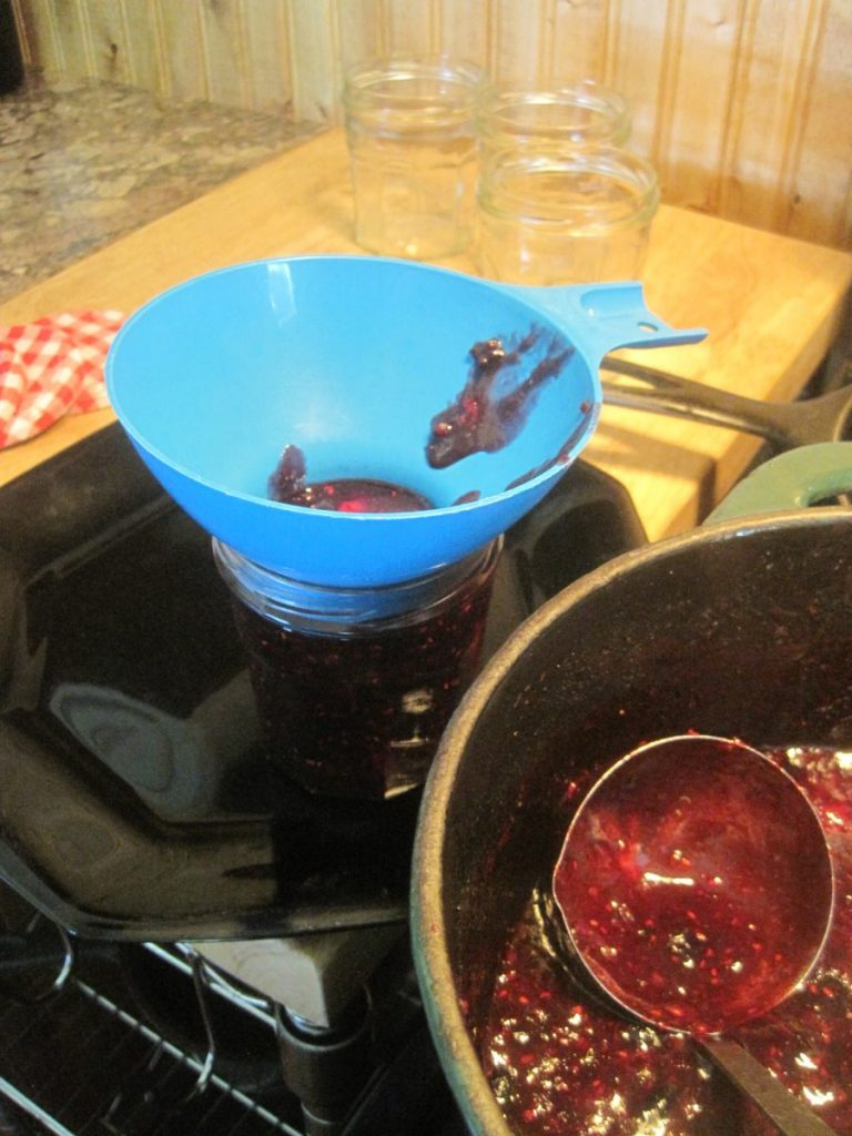 Ladling hot jam directly into the canning funnel and into the jars.