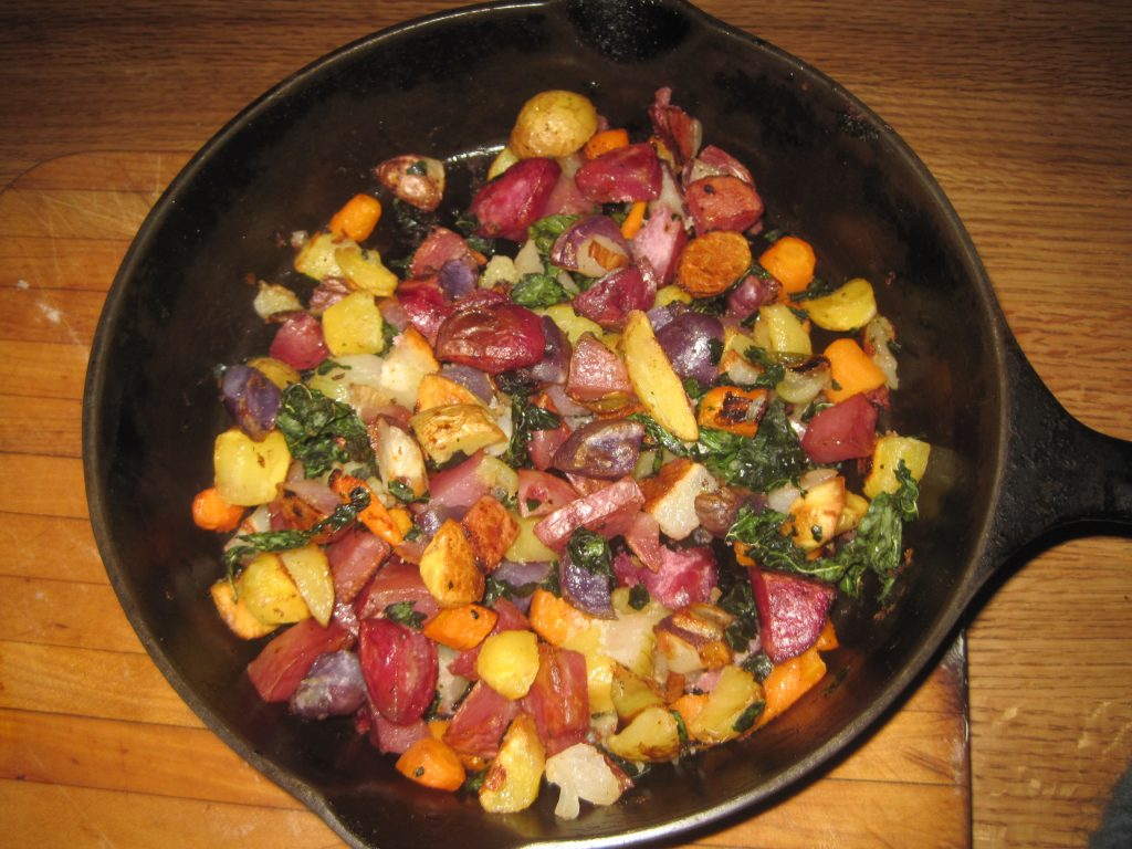 Oven Roasted Colorful Potatoes, Carrots, Onions and Kale in black cast iron pan