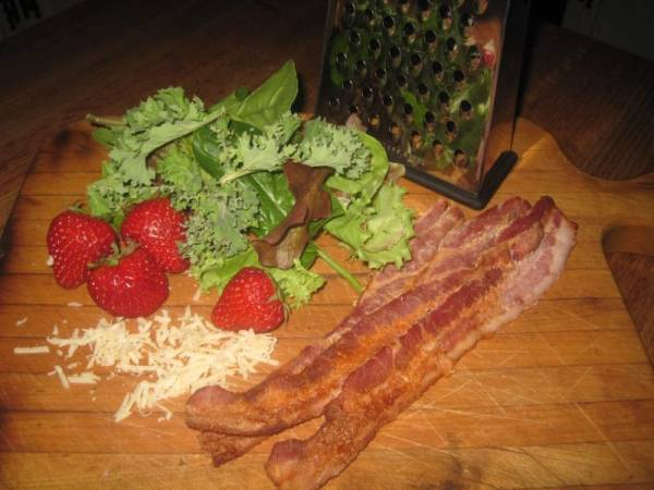 kale, strawberries, bacon, Parmesan cheese and a cheese grater