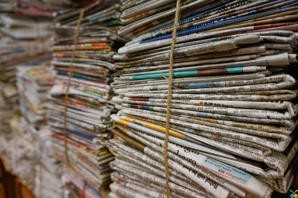 stacks of old newspapers that can be used for mulch in garden rows