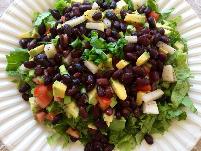 a healthy salad recipe with beans and avocado on a white plate