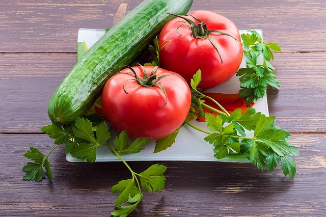tomatoes, cucumber and cilantro on a square white plate