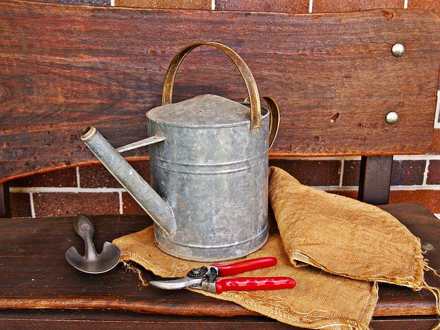 watering can, burlap bag, garden clippers and a small trowel on a wooden bench